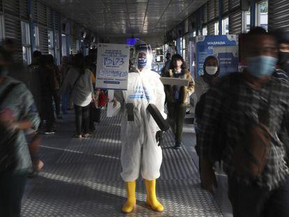 Un empleado sujeta una pancarta con información sobre el virus en una estación de autobuses de Yakarta.