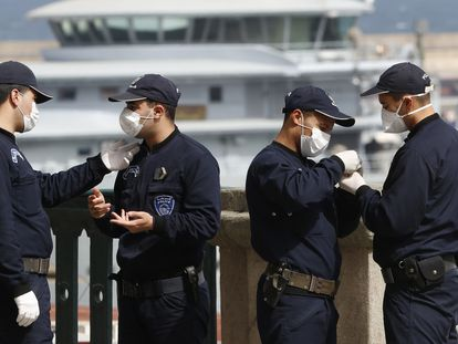 Agentes argelinos portan máscaras mientras un crucero llega al puerto de Argel el jueves 19 de marzo.