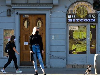 Una mujer pasea frente a una tienda de cambio de bitcoin en el centro de la ciudad de Cracovia (Polonia).