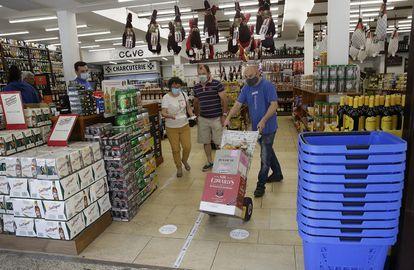 Varios clientes compran cajas de licor en Behobia a las nueve de la mañana de este domingo.