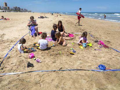 Valencia pasa a Fase 2. Dos familias que conviven en una de las parcela de prueba en la playa de Gandia.
