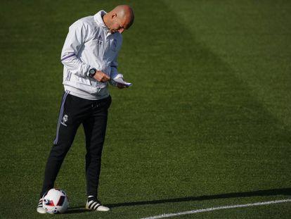 Zinedine Zidane revisa su libreta durante un entrenamiento.