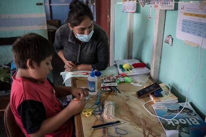 Jairo Chuquimán asiste a una clase  virtual a través del móvil el 12 de marzo de 2021 en presencia de su madre, Zaida Luján, en su casa del barrio 30 de Octubre de Perú, Lima. Pincha en la imagen para ver la fotogalería completa.