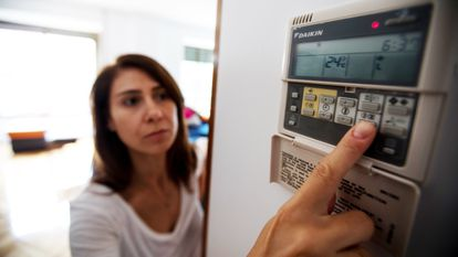 Una mujer acciona el panel del aire acondicionado en su vivienda.