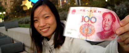 Una mujer sujeta un billete de 100 yuanes.