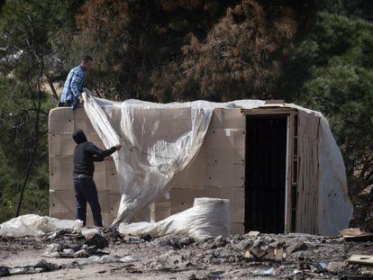 Dos temporeros reconstruyen una chabola calcinada, en un asentamiento de Palos de la Frontera (Huelva).