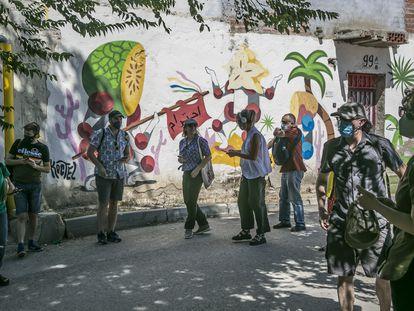 Varias personas recorren el sector V de la Cañada Real, escuchando audios con historias de sus vecinos.