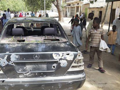 Ciudadanos junto a un coche dañado por el último ataque en la localidad nigeriana de Maiduguri, este miércoles.