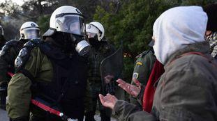 La policía antidisturbios se encara con un manifestante de un grupo que trata de bloquear la carretera próxima al lugar donde se construirá el centro de detención de migrantes, en la isla griega de Lesbos.