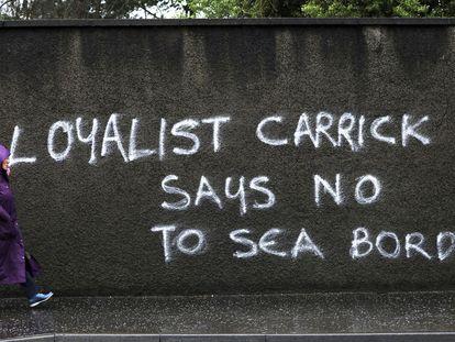 Una mujer pasa ante una pintada en contra de los controles aduaneros en el mar de Irlanda, este miércoles en Carrickfergus (Irlanda del Norte)