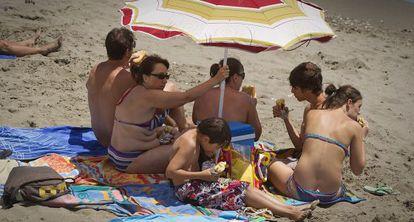 Una familia come sus bocadillos bajo la sombrilla en la arena de una playa de Benalmádena (Málaga).