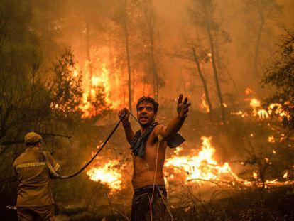 Un residente de la localidad de Pefki, en la isla de Eubea, hace un gesto mientras sostiene una manguera de agua vacía durante un intento de extinguir los incendios forestales que golpean a Grecia desde hace días.