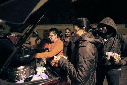 Dos de las voluntarias de Amigos de la Calle distribuyen la sopa de verduras entre varios <i>sin techo</i> de Valencia.