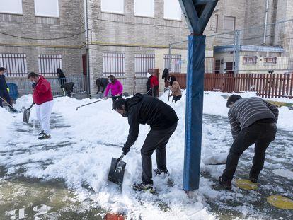 Grupo de padres voluntarios recogiendo nieve en el CEIP Victor Pradera de Leganés.