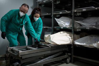 Dos empleados preparan el cuerpo de un fallecido para introducirlo en un ataúd, en el tanatorio Sancho de Ávila, en Barcelona.
