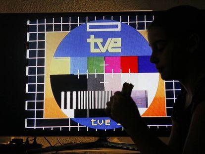 Una niña merienda frente a una televisión con una carta de ajuste de TVE.