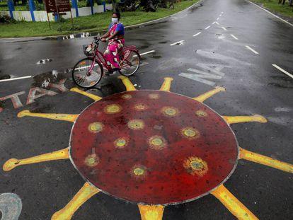 En India, las ONG antitrata se han visto desbordadas para poder ayudar a las supervivientes durante la pandemia. En la imagen, una mujer pedalea junto a un dibujo del SARS-CoV-2 pintado sobre el asfalto en Calcuta, India.