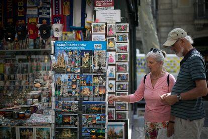 25/06/19 Dos turistas miran postales en un quiosco de la Rambla.