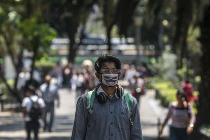 Un joven estudiante con mascarilla camina por la calle Génova, en Ciudad de México.