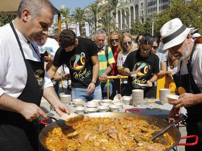 Dos cocineros emplatan una paella de marisco en la plaza del Ayuntamiento de Valencia.