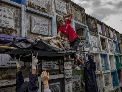 Trabajadores funerarios exhuman el cadáver de una de las víctimas de la guerra contra las drogas para incinerarlo tras terminarse el alquiler del nicho en el que se encontraba.