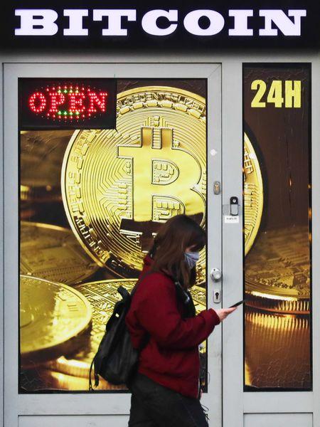 Una donna passa davanti a un negozio di bitcoin a Cracovia il 2 gennaio.