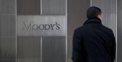 Un hombre ante un cartel de Moddy's en las oficinas de la empresa en Nueva York