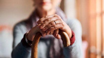 Un anciana se apoya sobre su bastón.