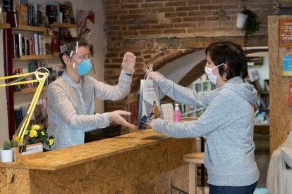 Una clienta con cita previa recoge su pedido en la librería La Carbonera, en el barrio de Poble Sec de Barcelona.