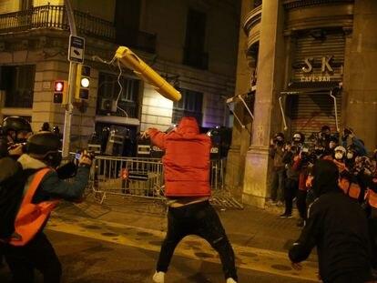 Un manifestante tira un objeto hacia las fuerzas de seguridad, este domingo en Barcelona.