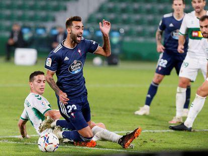 El centrocampista del Celta Brais Méndez cae en el área del Elche tras una entrada de Iván Marcone.