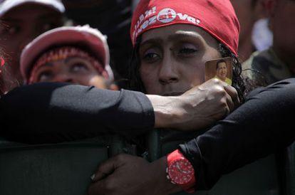 Una chavista sujeta un recordatorio de Chávez mientras espera el paso del cortejo funerario hacia una academia militar en Caracas.