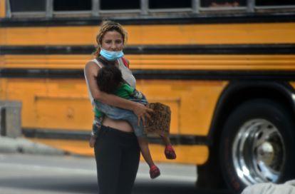 Una mujer con un niño en brazos, pide dinero en las calles de Tegucigalpa, Honduras.