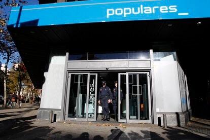 Agentes la Policía Nacional, en la puerta de la sede del PP en la calle Génova, de Madrid, durante el registro realizado en diciembre de 2013.