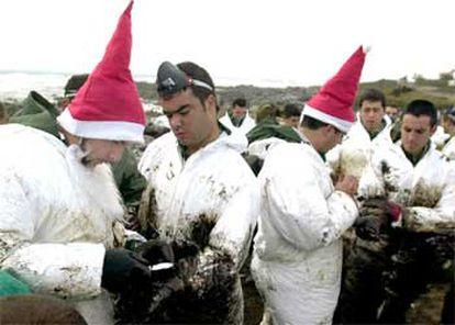 Soldados tocados como Papá Noel ayudan a limpiarse a sus compañeros en la playa de Lira.
