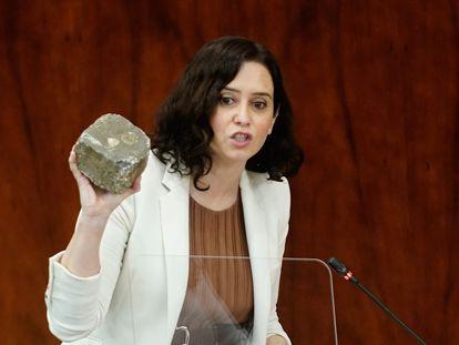 La presidenta de la Comunidad de Madrid, Isabel Díaz Ayuso, mostrando en la Asamblea de Madrid un adoquín que se arrojó durante los incidentes del miércoles en Puerta del Sol.