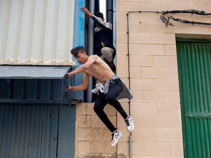 Dos menores migrantes se escapan de la nave del polígono industrial cercano a la playa de El Tarajal de Ceuta, este viernes.