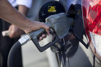 Un hombre pone gasolina en su coche.