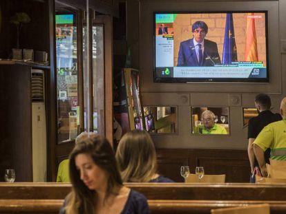 Varios personas siguen la intervención de Puigdemont este jueves.