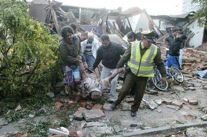 Un policía chileno y varios vecinos sacan el cadáver de un hombre de una casa totalmente destruida por el terremoto en Talca, a 275 kilómetros al sur de Santiago.