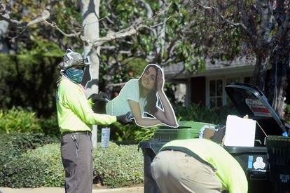 Un miembro del equipo de limpieza deposita un cartel de Ana de Armas en la basura frente a la casa de Ben Affleck, en Los Ángeles el pasado lunes.