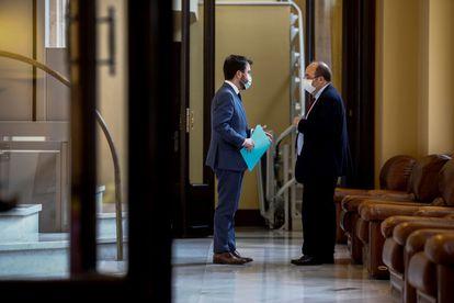 El 'president' en funciones del Govern, Pere Aragonés (i), habla ayer con líder del PSC, Miquel Iceta (d), en la puerta del hemiciclo del Parlament