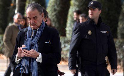 Mario Conde consulta su teléfono móvil a la salida de la Audiencia Nacional, en Madrid.