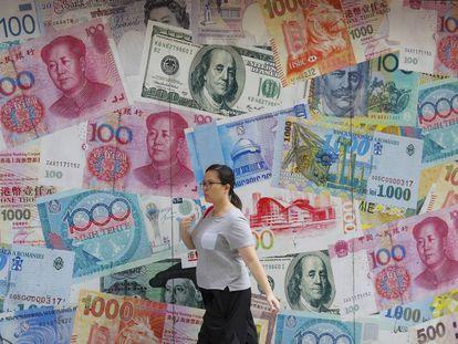 Una mujer pasa junto a una oficina de cambio en Hong Kong.