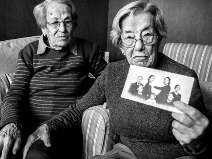 Las hermanas Lucía y Juana Molina Casado, que tienen 100 años, muestran un montaje fotográfico hecho para integrar en el retrato a los familiares ausentes.