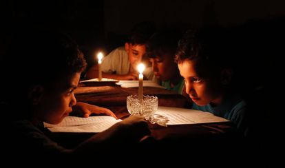 Niños palestinos estudian en Gaza a la luz de las velas a causa de los apagones.