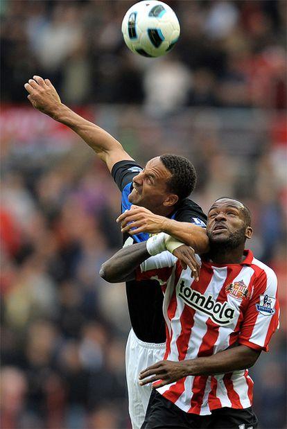Ferdinand y Bent disputan un balón aéreo.