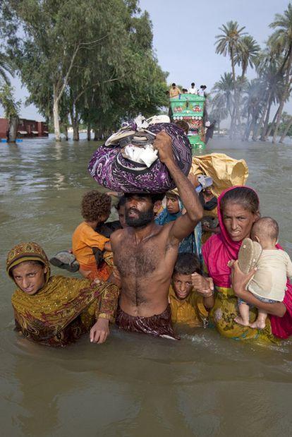 Una familia paquistani camina con el agua por la cintura por el distrito totalmente inundado de Punjab, provincia de Muzaffargarh.
