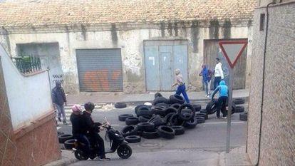 Un grupo de personas  levanta una barricada en la entrada del barrio melillense de la Cañada.