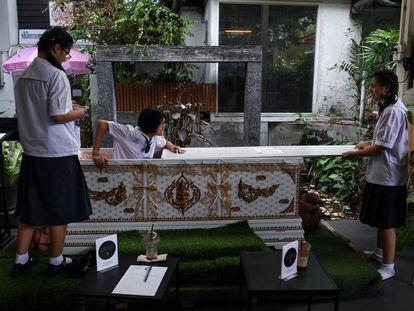 Una joven sale del ataúd instalado como parte de la decoración en el Kid Mai Cafe de Bangkok.